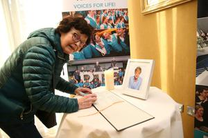 Ruth Barror signs the book. Photo: Stephen Collins/Collins Photos