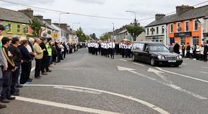 The village of Charlestown comes together as the remains of Det Garda Colm Horkan remains are carried through the town.  Picture; Gerry Mooney
