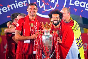 ON HIS WAY: Liverpool's Dejan Lovren (left) and Mohamed Salah celebrate with the Premier League trophy