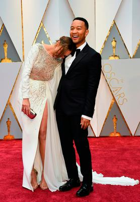 John Legend (R) and US model and wife of John Legend Chrissy Teigen arrive on the red carpet for the 89th Oscars on February 26, 2017 in Hollywood, California.  / AFP PHOTO / VALERIE MACONVALERIE MACON/AFP/Getty Images