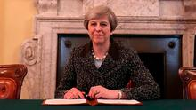 Prime Minister Theresa May signs the Article 50 letter in her London office yesterday before it was dispatched to Brussels to be handed over this morning. Photo: PA