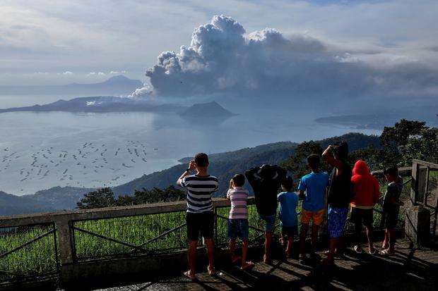 Ash cloud: Residents look at the erupting Taal volcano in Tagaytay City, Philippines. Photo: REUTERS/Eloisa Lopez