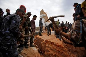 Rescuers remove debris at the historic Dharahara tower, a city landmark, after an earthquake in Kathmandu, Nepal, Saturday, April 25, 2015. A strong magnitude-7.9 earthquake shook Nepal's capital and the densely populated Kathmandu Valley before noon Saturday, causing extensive damage with toppled walls and collapsed buildings, officials said. (AP Photo/ Niranjan Shrestha)