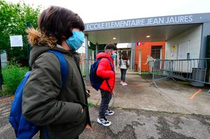 Children wait in line with security distance to enter primary school in western France after an almost two-month closure due to the lockdown imposed. (Photo by MEHDI FEDOUACH / AFP) (Photo by MEHDI FEDOUACH/AFP via Getty Images)