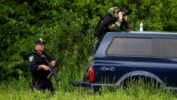 Law enforcement officers look out over a field near Willsboro, New York June 9, 2015. REUTERS/Chris Wattie