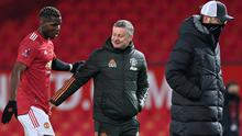 A job well done: Manchester United manager Ole Gunnar Solskjaer with Paul Pogba after the match as Liverpool boss Jurgen Klopp leaves the pitch after the game. Photo: Reuters