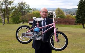 DC Fred Hunter from the media crime unit holds a bike belonging to April Jones' friend, (who cannot be named), in Mold, north Wales, as the jury has today viewed a car belonging to murder suspect Mark Bridger