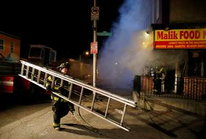 A Baltimore firefighter rushes a ladder into place to attack a fire set by rioters in a convenience store and residence on East Biddle Street and Montford Avenue during rioting in Baltimore, Maryland in the early morning hours of April 28, 2015. REUTERS/Jim Bourg