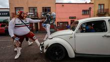 Convincing tactics: Mexican Lucha Libre wrestlers  stop a car to hand out masks as part of a local campaign to promote the use of face masks as a preventive measure against coronavirus in Xochimilco, Mexico. Photo: Getty