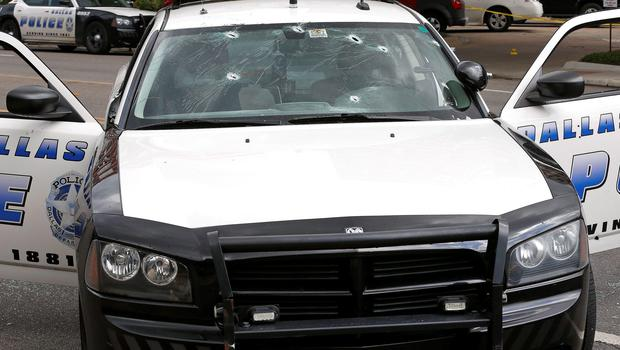 Bullet holes pierce the windshield of a police cruiser at Dallas Police Headquarters after an early morning attack on police by a gunman Saturday, June 13, 2015, in Dallas. (AP Photo/Ron Jenkins)