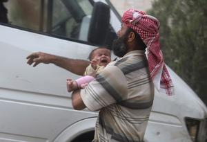 A man holds a baby who survived what activists said were airstrikes by forces loyal to Syria's President Bashar al-Assad, in the Duma neighbourhood of Damascus. Reuters/Bassam Khabieh