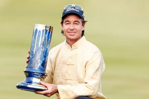 Brett Rumford of Australia celebrates with the trophy after winning the final round of the Volvo China Open
