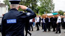 A garda salutes Detective Garda Colm Horkan, as his coffin is carried through Charlestown yesterday. Photo: Gerry Mooney