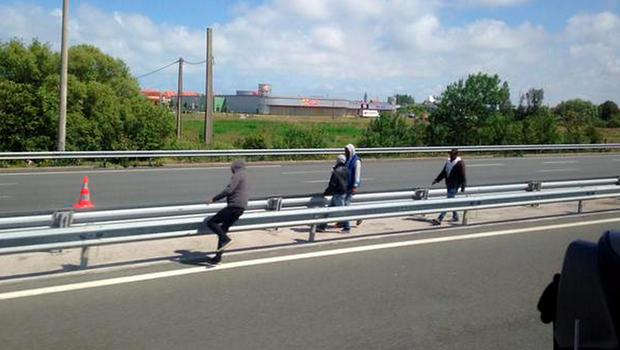 Migrants by the side of a road in Calais as French ferry workers strike.