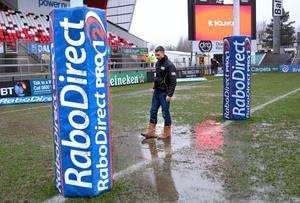 Referee Leighton Hodges insects the waterlogged Ravenhill pitch before calling the match off