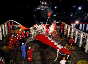 A section of the tail of AirAsia Flight QZ8501 passenger plane is seen on the deck of the rescue ship Crest Onyx, a day after it was lifted from the seabed, as crew try to lift it off the ship in  Kumai Port, near Pangkalan Bun, Central Kalimantan REUTERS/Darren Whiteside