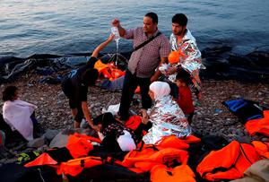 Volunteers provide medical help to a pregnant Syrian refugee woman shortly after she arrive with her family on a overcrowded dinghy at a beach on the Greek island of Lesbos after crossing a part of the Aegean Sea from the Turkish coast, September 19, 2015.  REUTERS/Yannis Behrakis