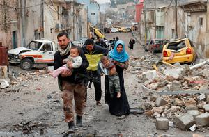 A soldier helps a family carry their child to the Iraqi forces-controlled part of Mosul. Photos: Reuters