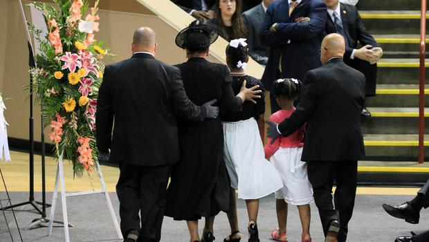 The family of  Rev. Clementa Pinckney is guided at his funeral service in the  TD Arena in Charleston, South Carolina, June 26, 2015.  President Barack Obama delivered the eulogy for Pinckney, the pastor of the historic church where the attack took place. Pinckney was one of the nine victims of the mass shooting at the church. REUTERS/Paul Zoeller/Pool