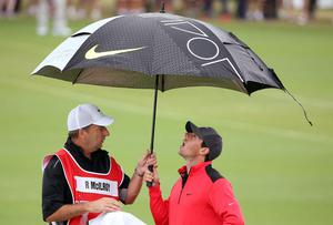 Ireland's Rory McIlroy, right, and his caddy JP Fitzgerald shelter under an umbrella during the first round of the Australian Open. AP Photo/Rick Rycroft