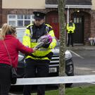 A woman leaving flowers left at the scene where two boys and a girl were found dead in a house at Parson's Court in Newcastle village, northwest of Rathcoole last night Picture by Fergal Phillips.