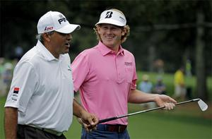 Brandt Snedeker chats with Angel Cabrera as they walk down the second fairway during the fourth round