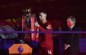 Soccer Football - Premier League - Liverpool v Chelsea - Anfield, Liverpool, Britain - July 22, 2020 Liverpool's Jordan Henderson  celebrates with the trophy after winning the Premier League Pool via REUTERS/Paul Ellis EDITORIAL USE ONLY. No use with unauthorized audio, video, data, fixture lists, club/league logos or 'live' services. Online in-match use limited to 75 images, no video emulation. No use in betting, games or single club/league/player publications.  Please contact your account representative for further details.