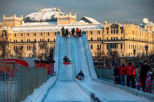 Children in inflatable rings slide down a snow slope  near Red Square with the historical Metropol Hotel in the background in Moscow, Russia, Monday, Jan. 9, 2017, as the temperature had plunged to minus -21 Celsius (minus-6 F) . (AP Photo/Alexander Zemlianichenko)