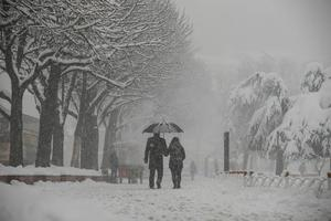A couple walk under an umbrella during snowfall in a park in Istanbul, Monday, Jan. 9, 2017. Heavy snow clogged roads, and Turkish Airlines on Monday canceled 277 domestic and international flights to and from Istanbul's two airports due to heavy snow. (AP Photos/Emrah Gurel)