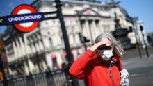a woman is seen wearing a protective face mask outside an Underground station in London. Photo: REUTERS/Hannah McKay