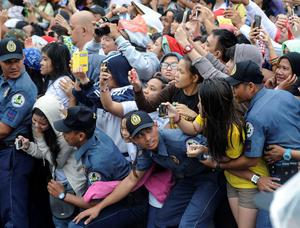 Members of the Philippine National Police prevent well-wishers from moving forward as Pope Francis' motorcade passes by in Manila January 18, 2015. REUTERS/Ezra Acayan