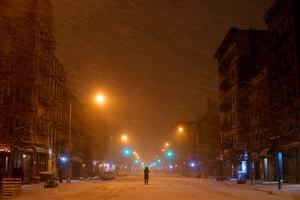 A person stands in the middle of snow-covered Avenue A in the East Village neighborhood of New York, early Tuesday, Jan. 27, 2015. (AP Photo/Patrick Sison)