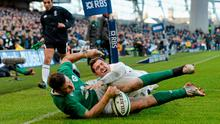 Robbie Henshaw scores Ireland's first try despite the tackle of Alex Goode, England