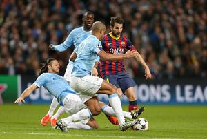 Barcelona's Francesc Fabregas is tackled by Manchester City's Martin Demichelis