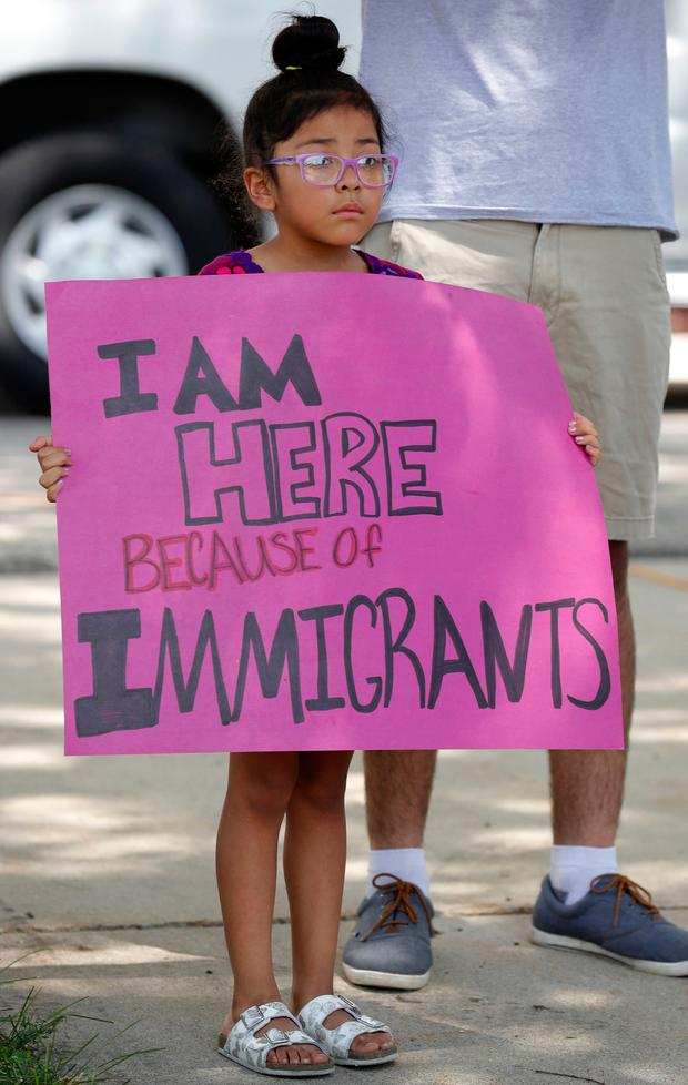 Five-year-old Alexa Gonzalez, of Marshalltown, Iowa, holds a sign during a rally to protest the Trump administration's immigration policies, Saturday, June 30, 2018, outside the Marshall County Courthouse in Marshalltown, Iowa. (AP Photo/Charlie Neibergall)