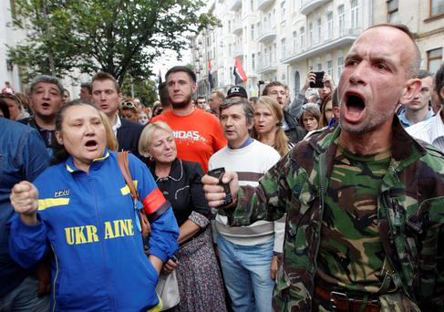 Public activists and relatives of soldiers who they say are surrounded by pro-Russian separatists in eastern Ukraine, shout slogans during a protest in front of the Presidential Administration office in Kiev, August 27, 2014.