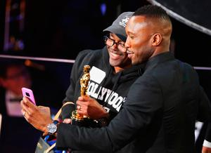 Mahershala Ali poses for a selfie with a man during a skit at the Oscars. REUTERS/Lucy Nicholson