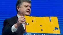 "Ukrainian President Petro Poroshenko shows a piece of a Bus that was attacked recently during the panel ""The Future of Ukraine"" in Davos, Switzerland (AP Photo/Michel Euler)"