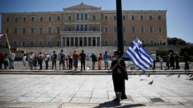 A woman holds a Greek flag with a smaller Cypriot flag attached to it during a May Day rally in front of the parliament in Athens