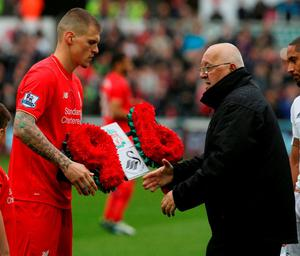 Liverpool  captain Martin Skrtel presents a wreath to Brian Devonside, father of Hillsborough victim Christopher Devonside, in memory of the 96 victims of the 1989 Hillsborough Distaster. Photo: Geoff Caddick/AFP/Getty Images