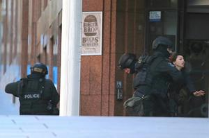 Armed tactical response police grab a hostage, right, as she flees from a cafe under siege at Martin Place in the central business district of Sydney, Australia. (AP Photo/Rob Griffith)
