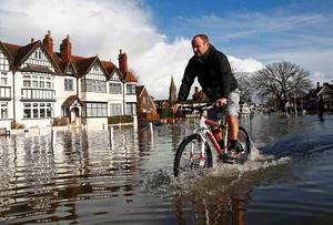 A resident cycles through deep water after the river Thames flooded the village of Datchet, southern England