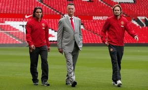 New Manchester United signings Radamel Falcao (L) and Daley Blind (R) walk with manager Louis Van Gaal