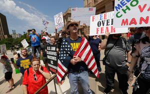 """Ignoring social distancing and mandates to wear masks for other face coverings, protesters attend an """"Open Texas"""" rally at the Texas State Capitol, Saturday, April 25, 2020, in Austin, Texas.  (AP Photo/Eric Gay)"""