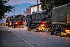 Italian military trucks drive through streets of Bergamo after the army were deployed to move coffins from the town.