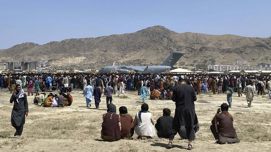 Hundreds of people gather near a US Air Force C-17 transport plane along the perimeter at the international airport in Kabul, Afghanistan (Shekib Rahmani/AP)