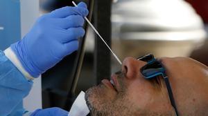 A health worker carries out a coronavirus test on a man outside a municipal administration building in the southern coastal city of Limassol, Cyprus. AP Photo/Petros Karadjias
