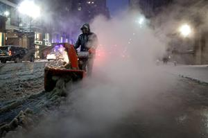 A worker pushes a snow blower down Lexington Avenue near Grand Central Terminal as it snows in the Manhattan borough of New York January 26, 2015.  REUTERS/Carlo Allegri