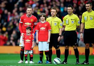 MANCHESTER, ENGLAND - MARCH 15:  Wayne Rooney of Manchester United runs out onto the pitch with his son Kai, who is a mascot for the day during the Barclays Premier League match between Manchester United and Tottenham Hotspur at Old Trafford on March 15, 2015 in Manchester, England.  (Photo by Michael Regan/Getty Images)