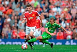 Sunderland's Lee Cattermole receives a booking for this challenge on Manchester United's French midfielder Morgan Schneiderlin